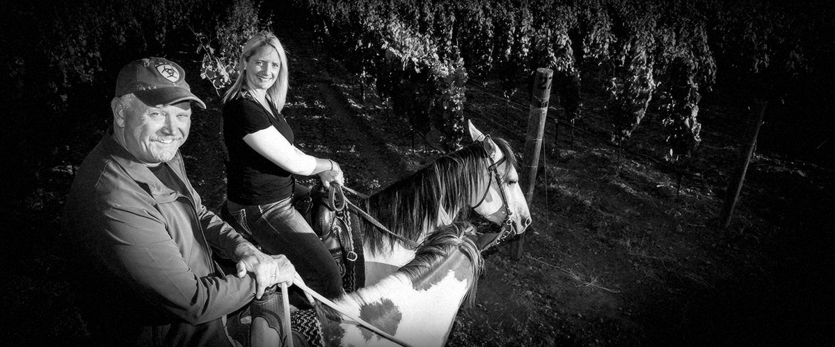 2Hawk Vineyard and Winery Owners Ross and Jen Allen Horseback Riding in Vineyard (Grayscale)