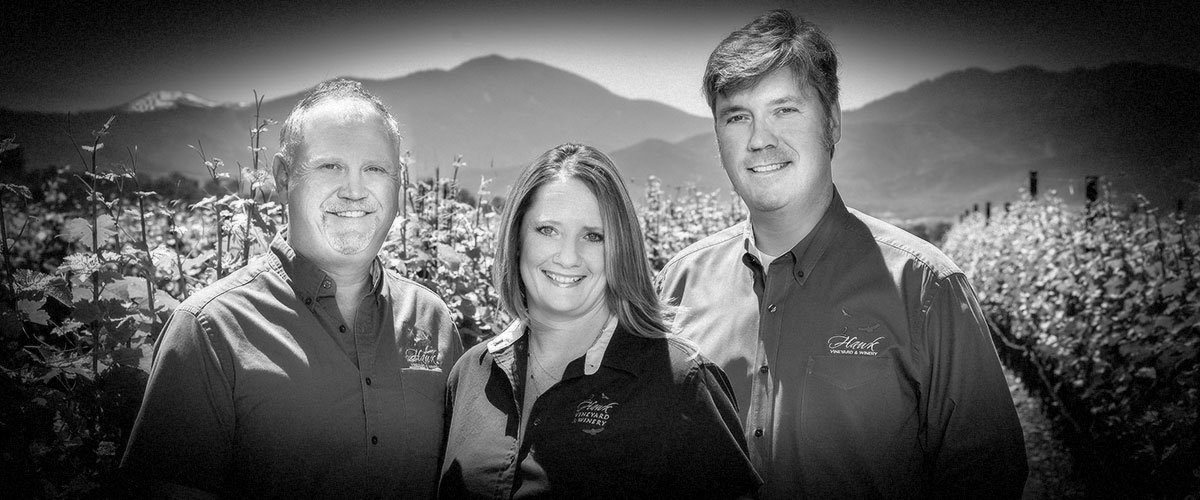 2Hawk Vineyard and Winery Team Ross Allen, Jen Allen, and Kiley Evans in Vineyard with Mountain Backdrop (Grayscale)